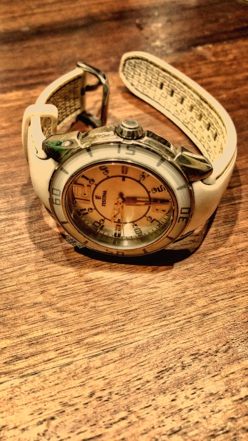 Round Silver-colored and White Analog Watch With White Rubber Band on Brown Wooden Surface