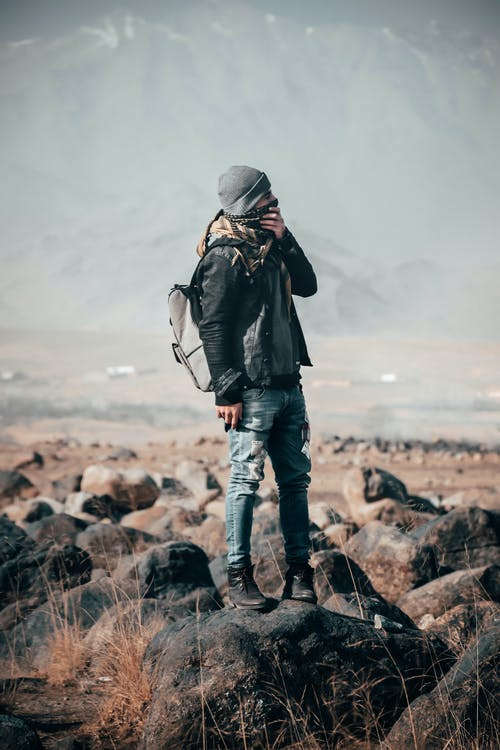 Man Wearing Black Jacket Standing on Gray Stone