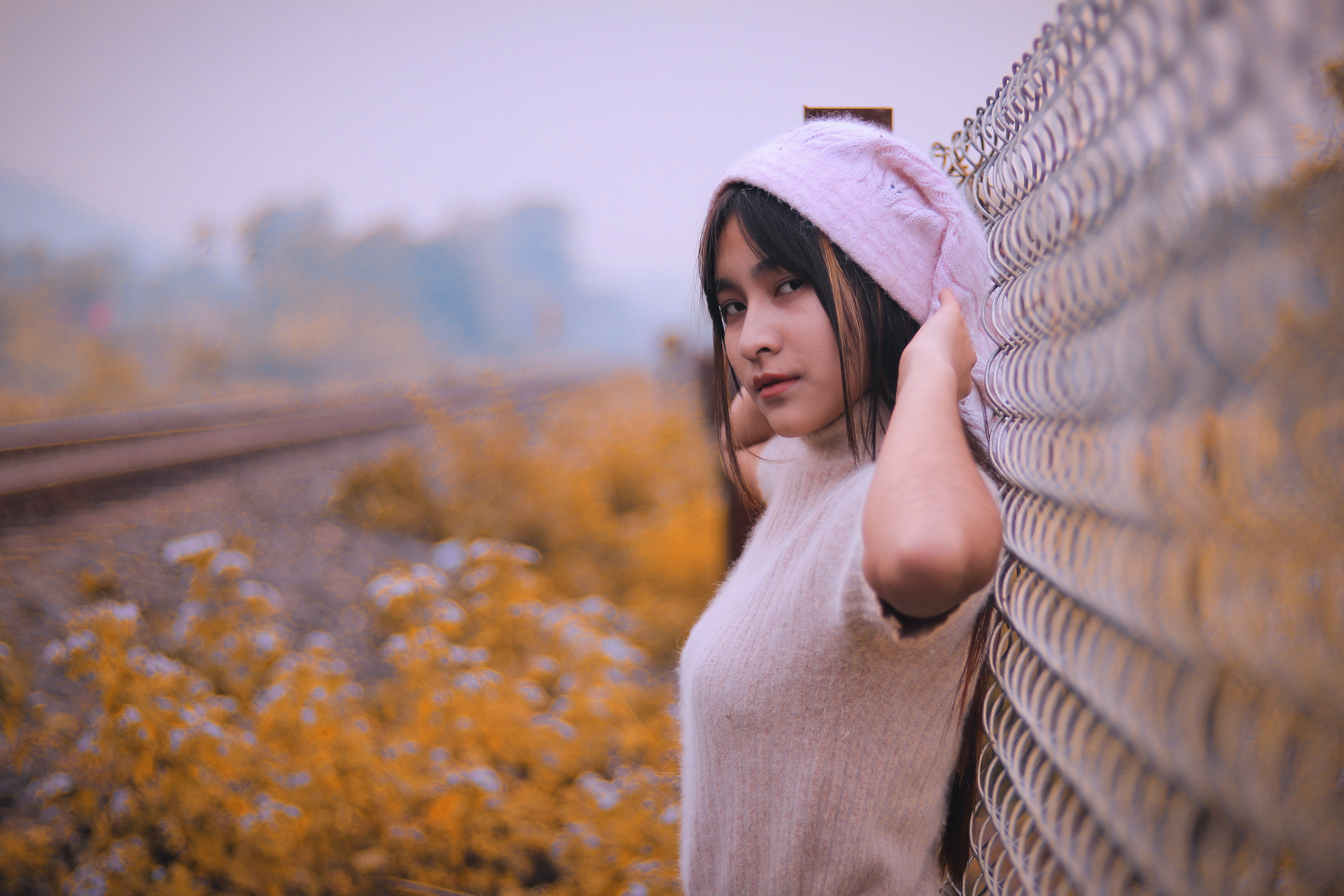 Woman Standing Beside Grey Fence