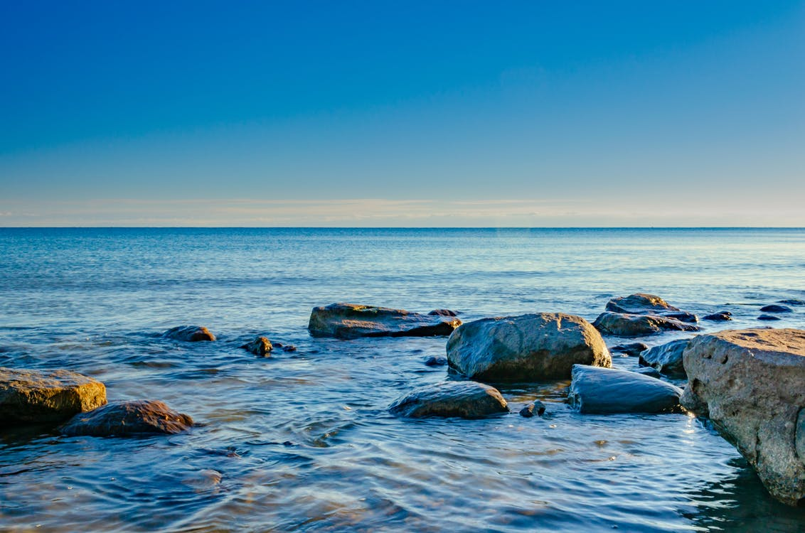 Rocks On Body Of Water Under Blue Sky