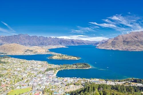 dağlar, küçük kasaba, Mavi gökyüzü, Mavi su içeren Ücretsiz stok fotoğraf