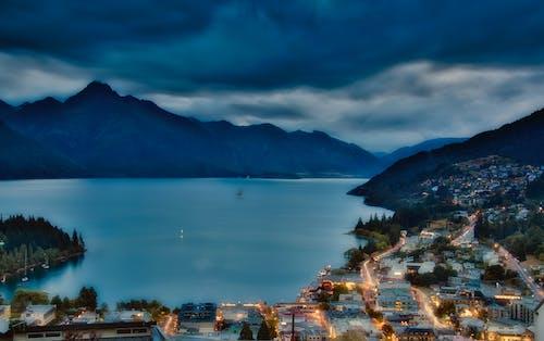 Akşam gökyüzü, dağlar, ışık çizgileri, küçük kasaba içeren Ücretsiz stok fotoğraf