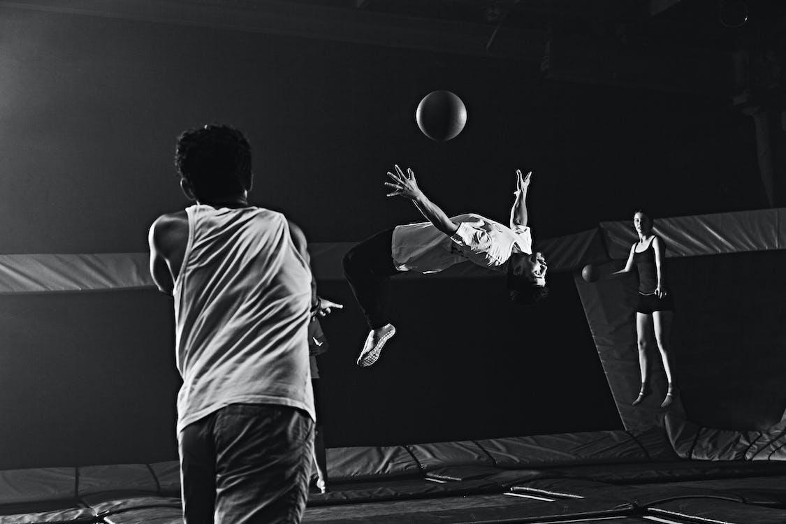 Grayscale Photography Of Man Doing Backflip