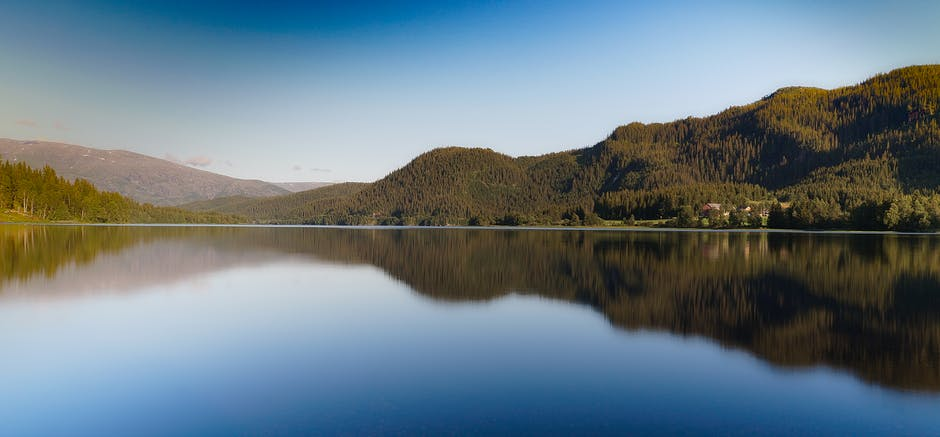 Brown calm body of water near mountains under blue sky at daytime