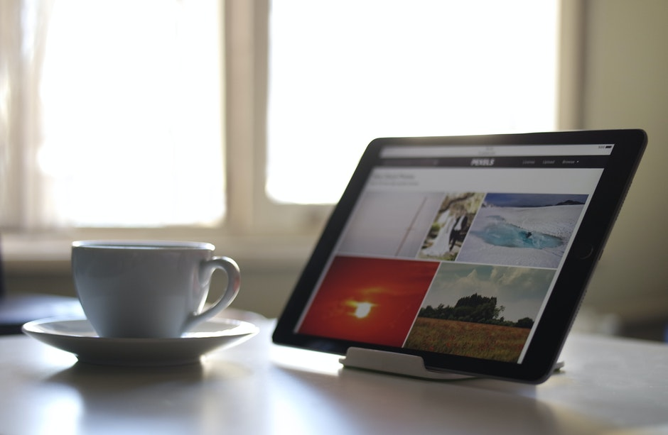 Black Tablet Computer Near a White Ceramic Teacup