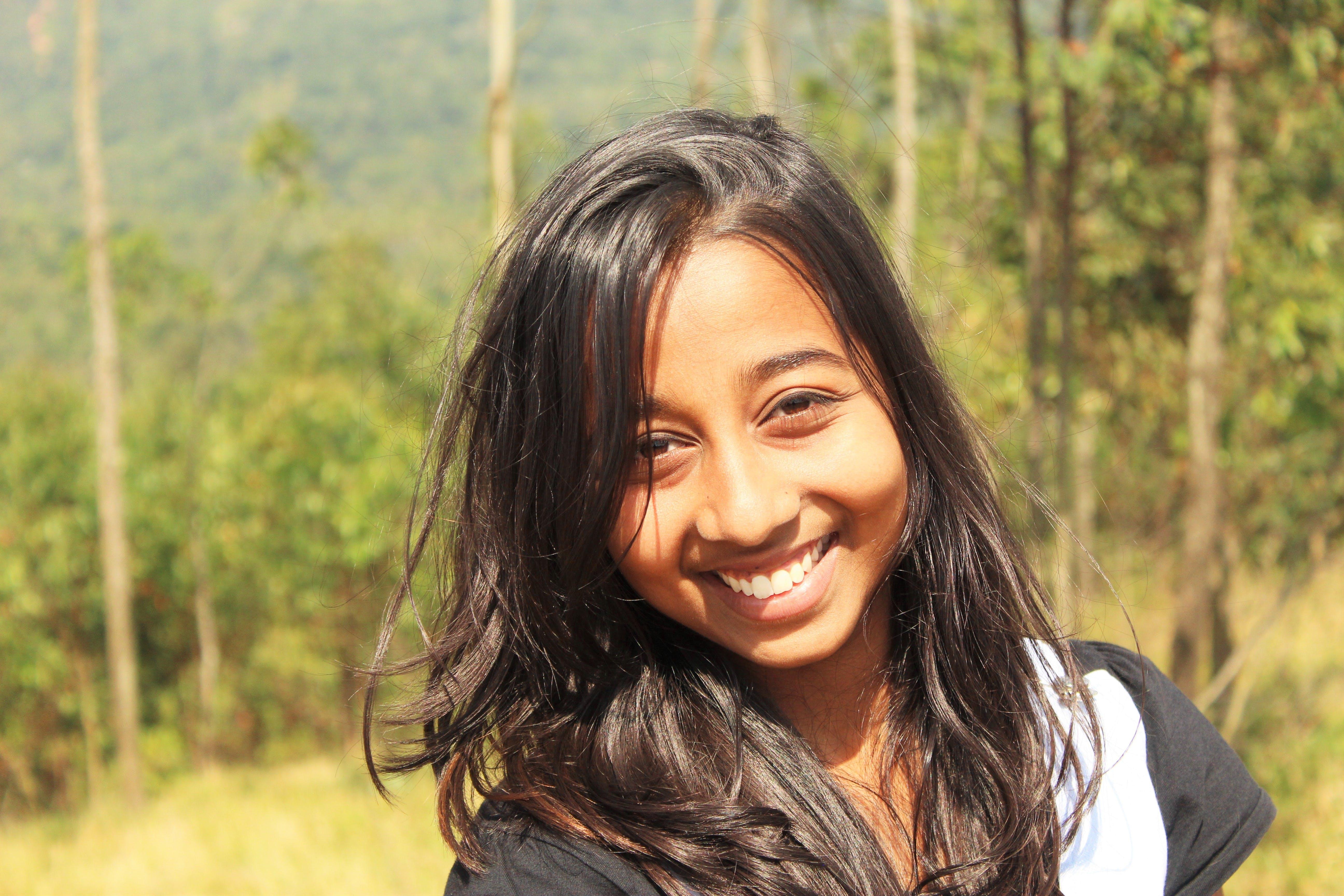 Kostenloses Stock Foto zu abenteuer mädchen, lächeln, lächelndes mädchen, mädchen im grünen hintergrund