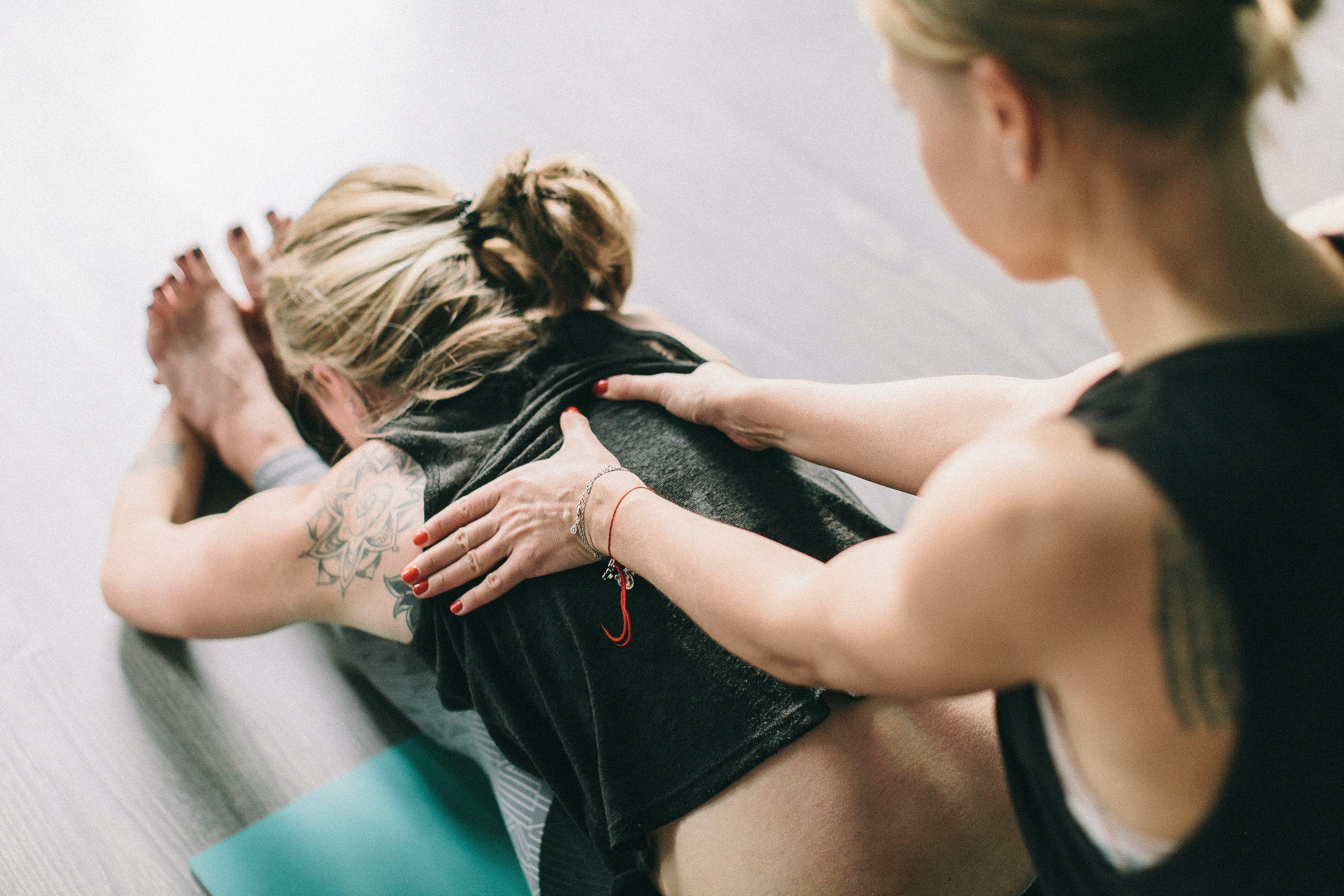 Woman Massaging Back Of Woman Sitting On Floor