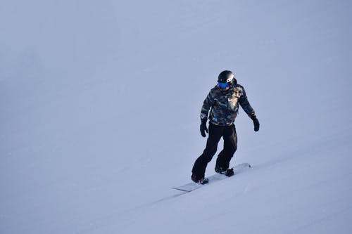 Photo of Person Snowboarding on Snow Covered Field