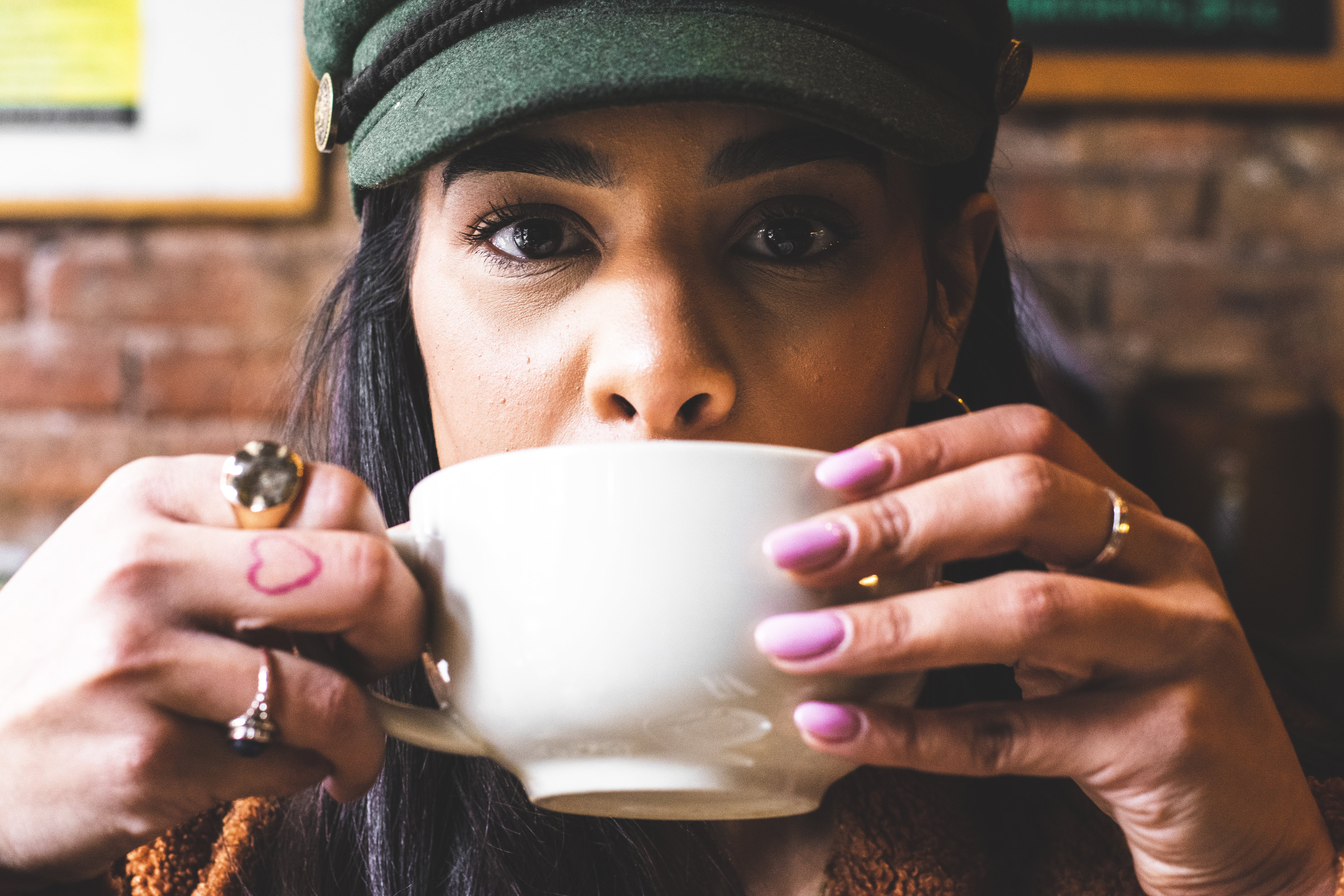 Woman Sipping in White Ceramic Teacup