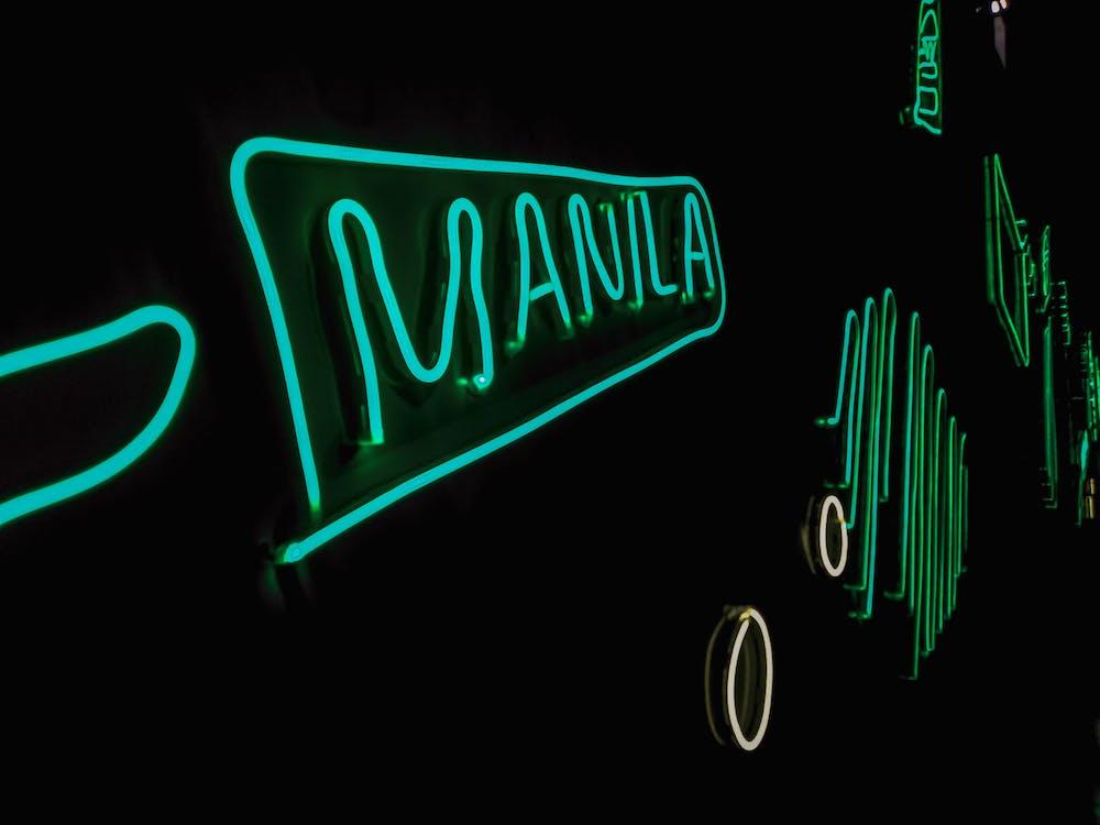 A stylish Manila signage in green neon light - Travel to Manila