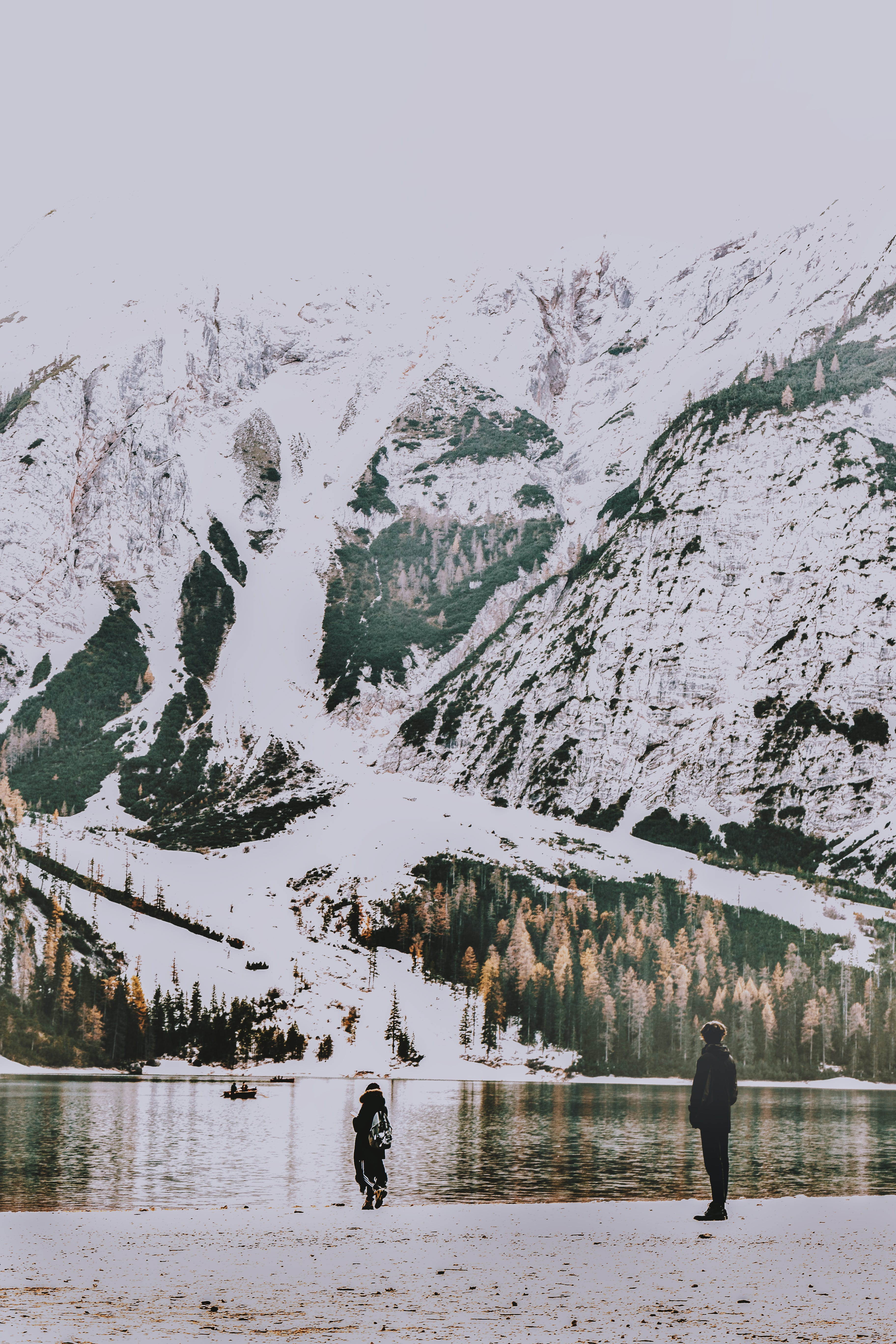 Two People Standing on Shore Overlooking Body of Water and Snow Covered Mountain