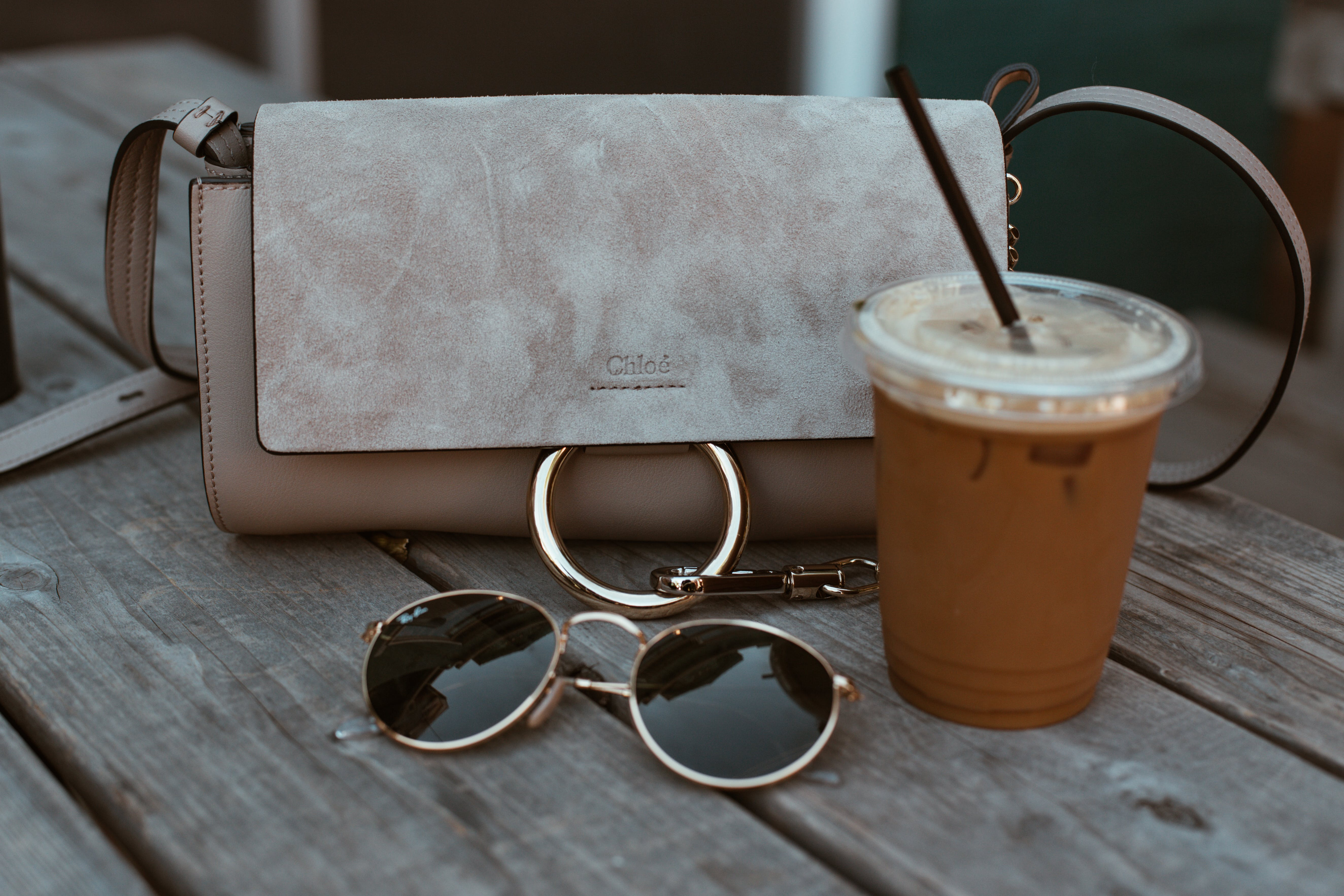 Leather Crossbody Bag Beside Drink And Sunglasses