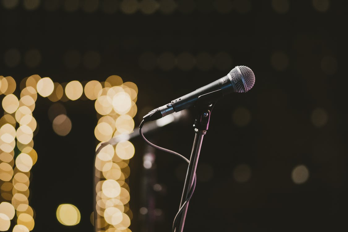 Selective Focus Photography Of Microphone On Microphone Stand