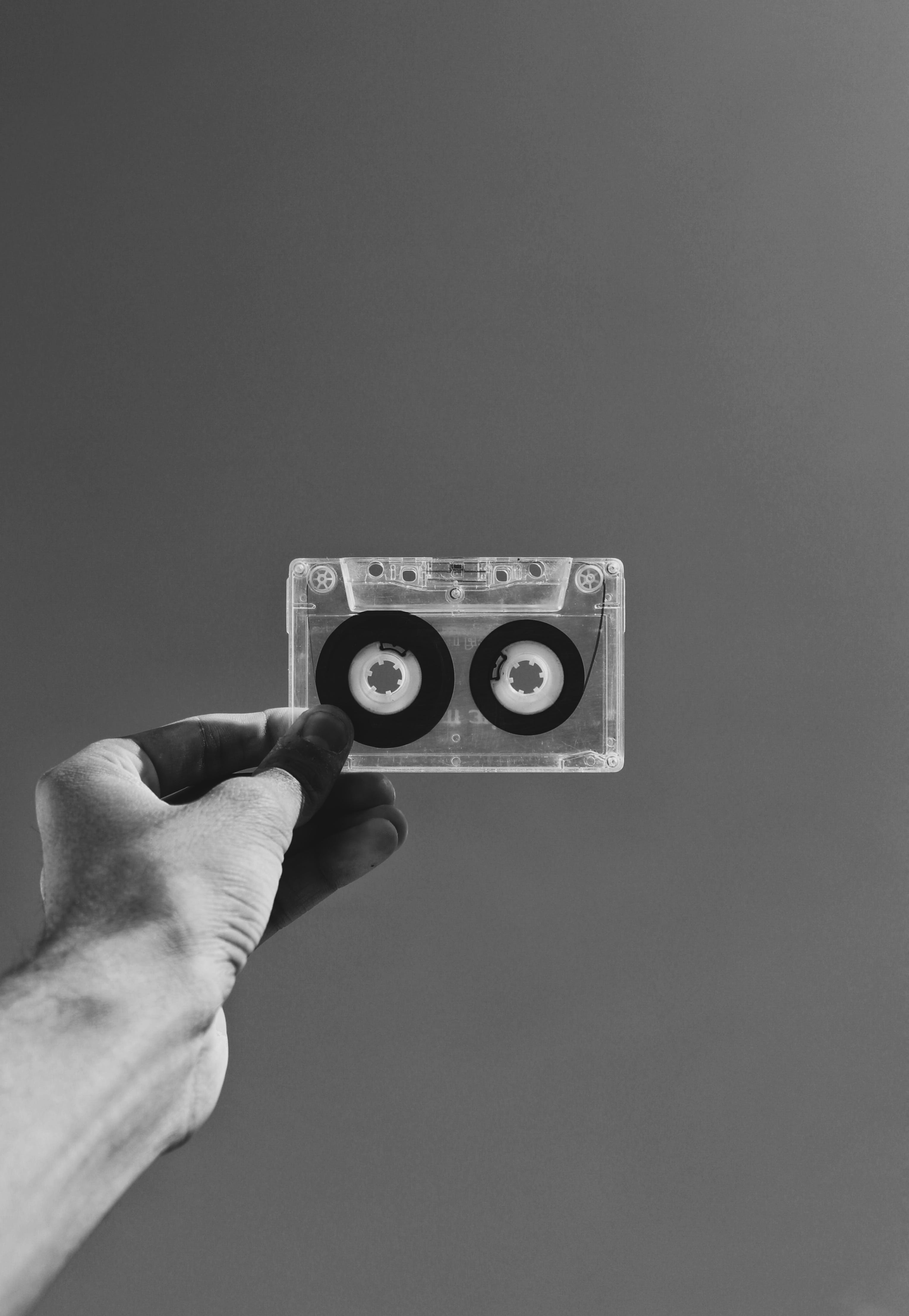 Grayscale Photography of Person Holding Cassette Tape