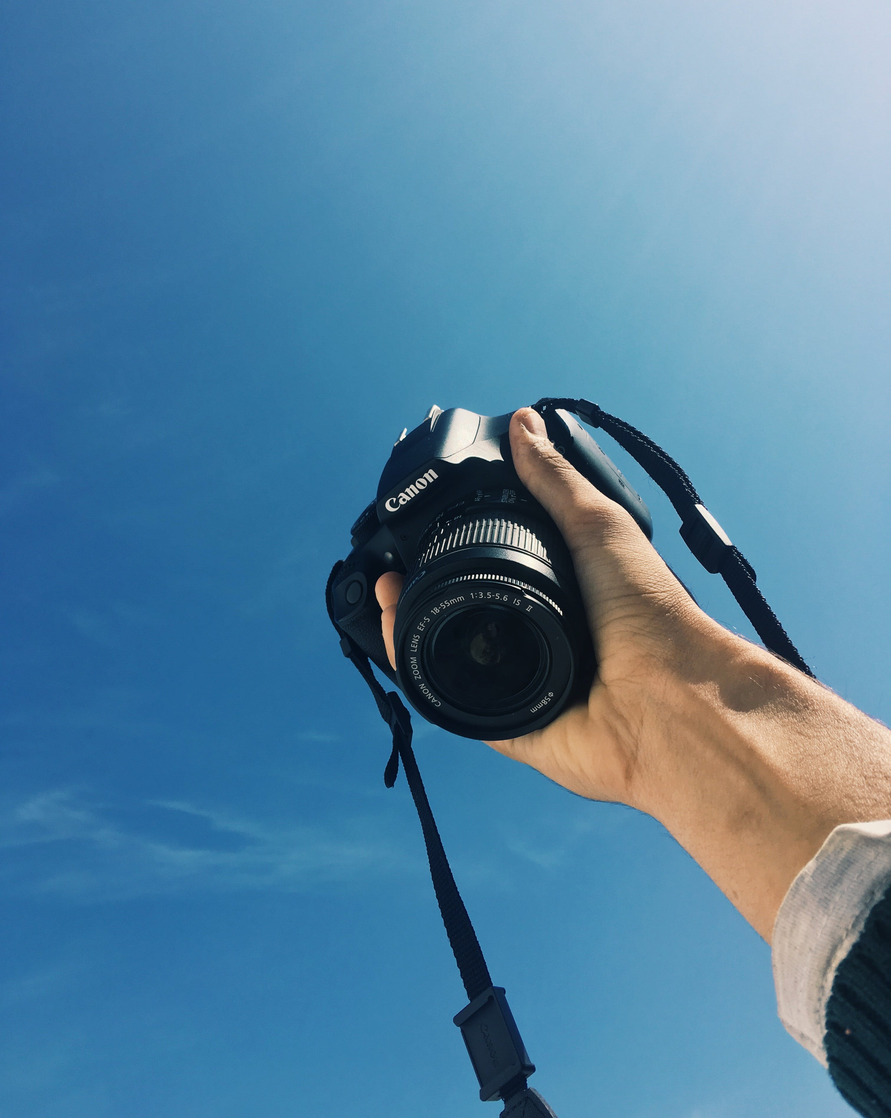 Kostnadsfri bild av blå himmel, dslr-kamera, hand, kanon