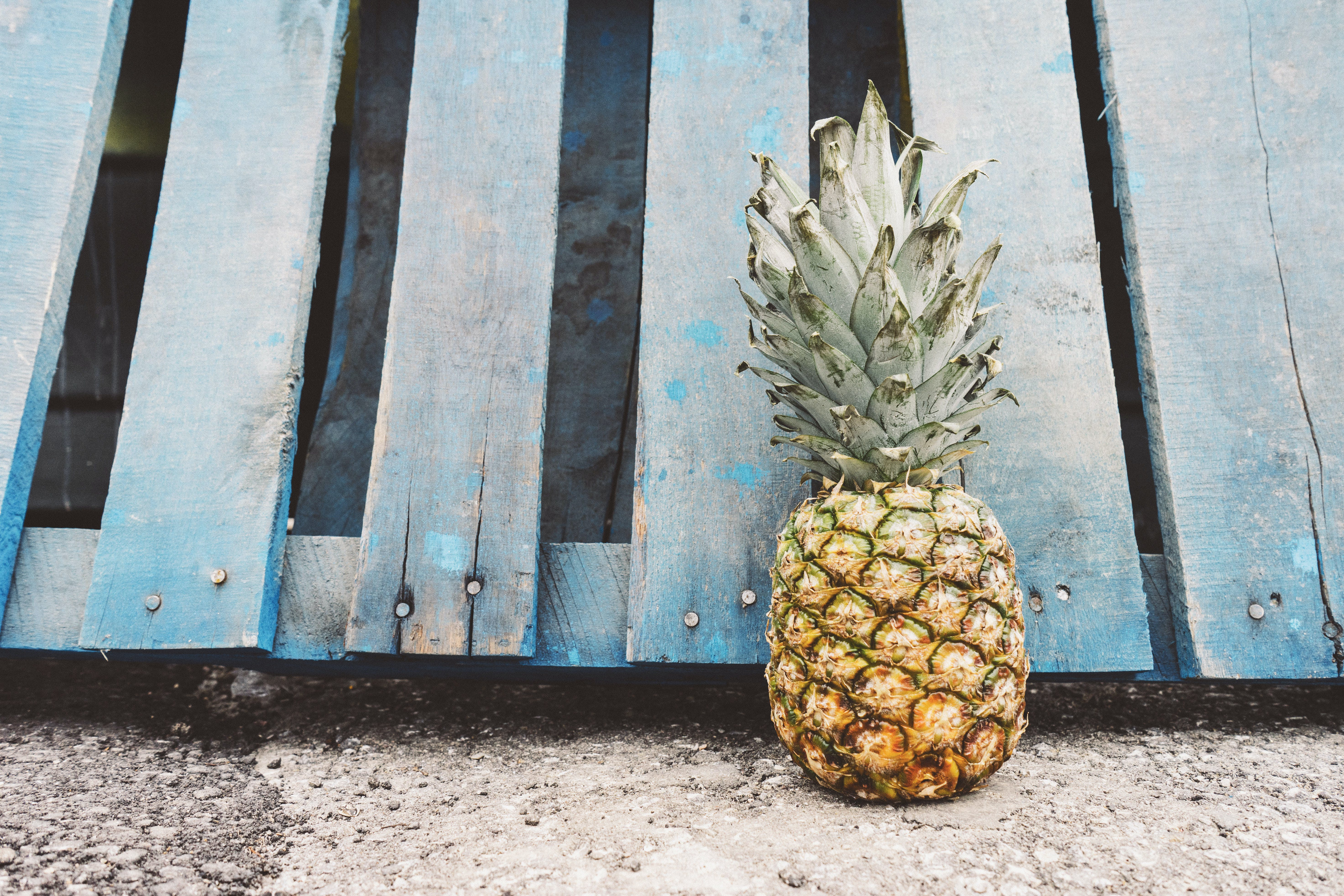 Yellow Pineapple Fruit Beside Blue Wooden Pallet
