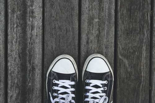 Black and White Sneakers on Grey Wooden Wood