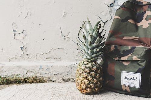 Pineapple Fruit Beside Black, Brown, and Beige Herchel Camouflage Backpack