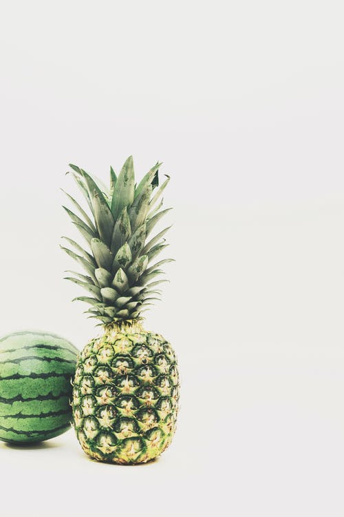 Photo of Green Pineapple and Watermelon Fruits Against White Background