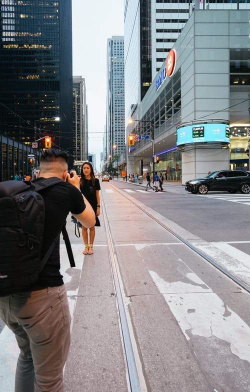 Man Taking Photo of Woman Standing Beside Highway Near Building