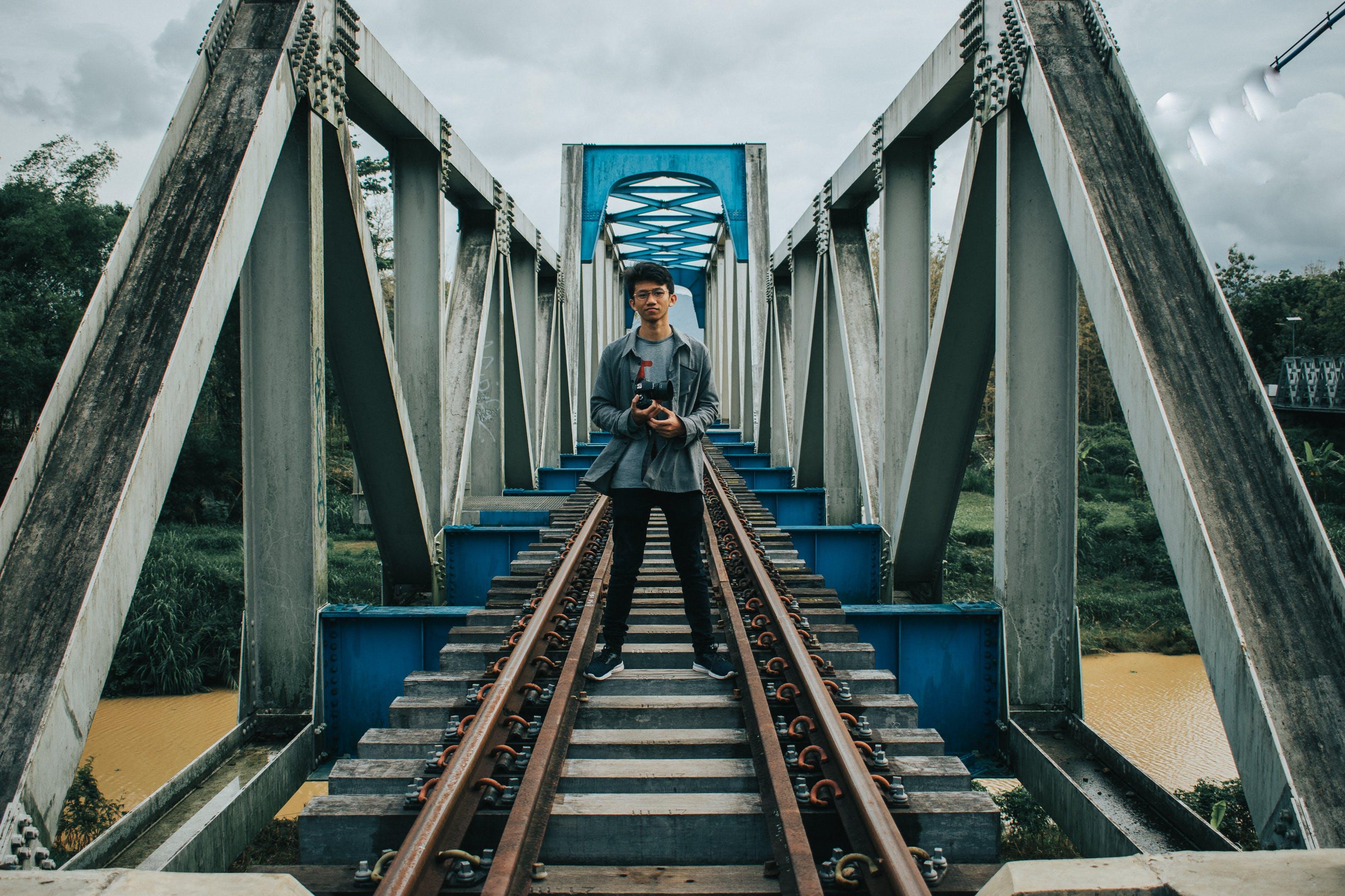 Man Standing on Train Tracks on Bridge Above Body of Water