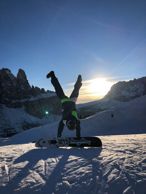 Photo of Person Doing Handstand Near Snowboard