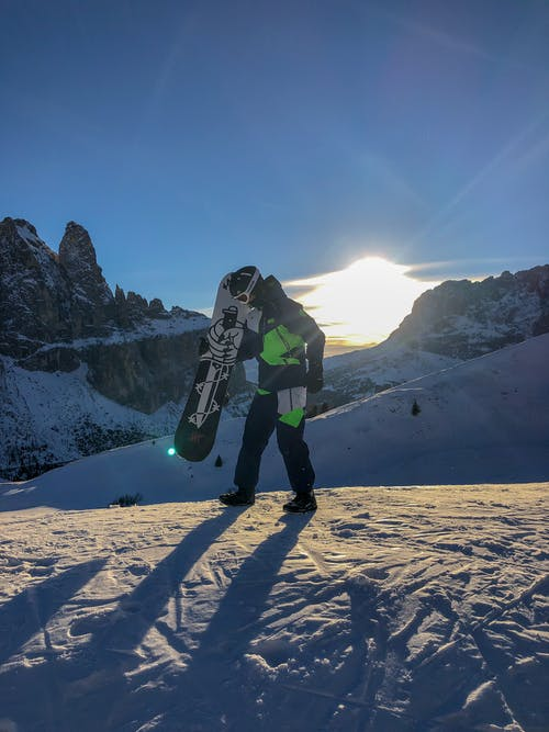 Man Holding Snowboard on Snowy Mountain