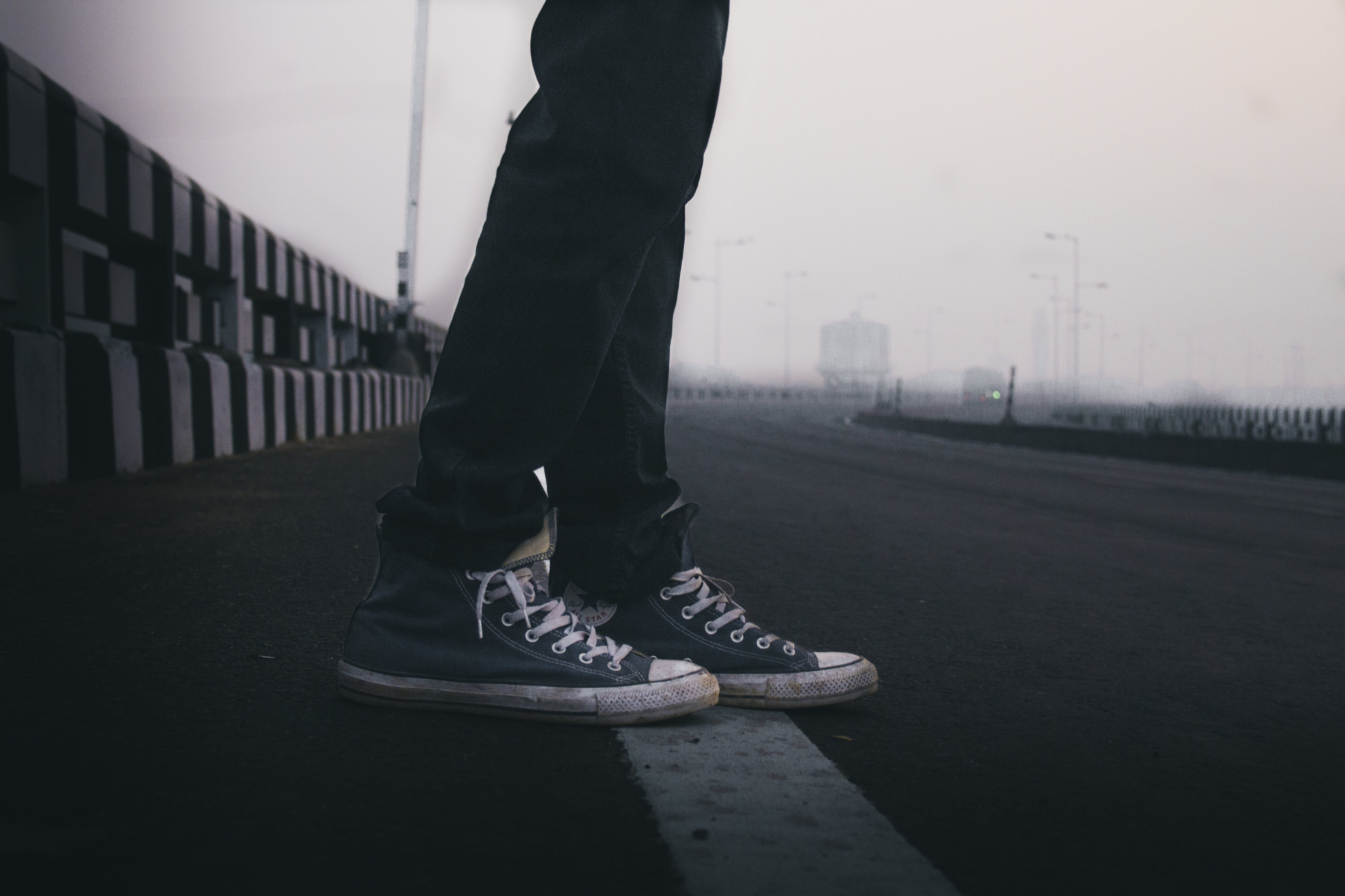 Person In Blue Sneakers Standing On Road