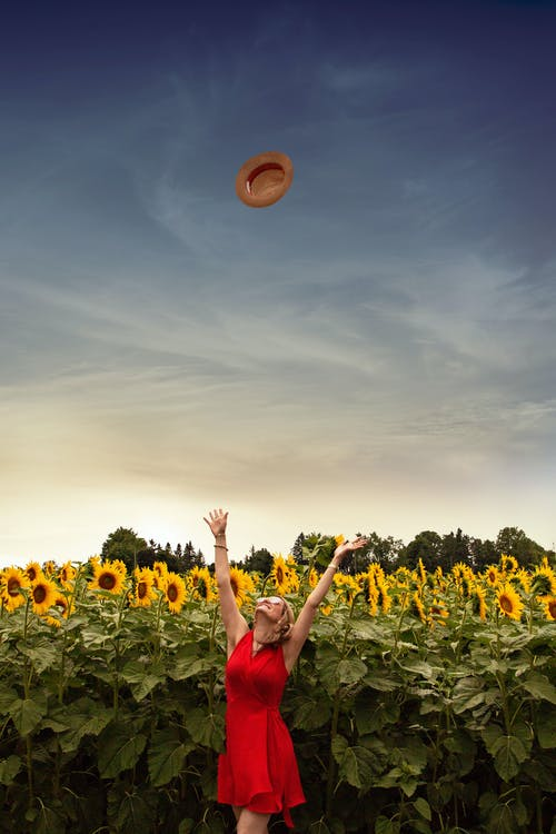 Photo of Woman Throwing Her Straw Hat Upwards