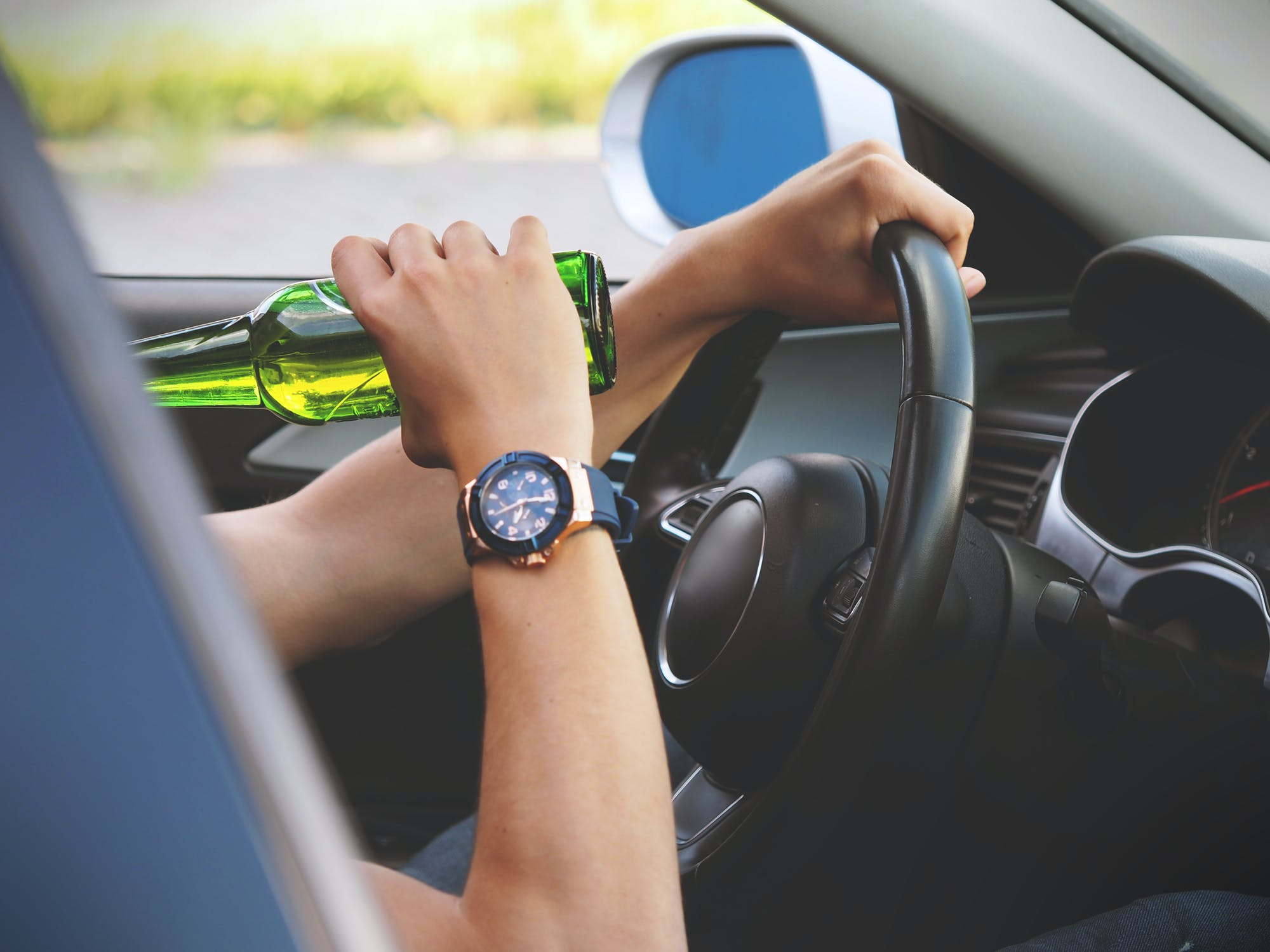 Person drinking a beer while driving