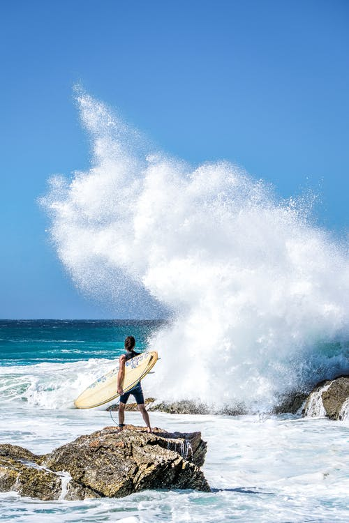 Person Holding Surfboard Standing On Rock