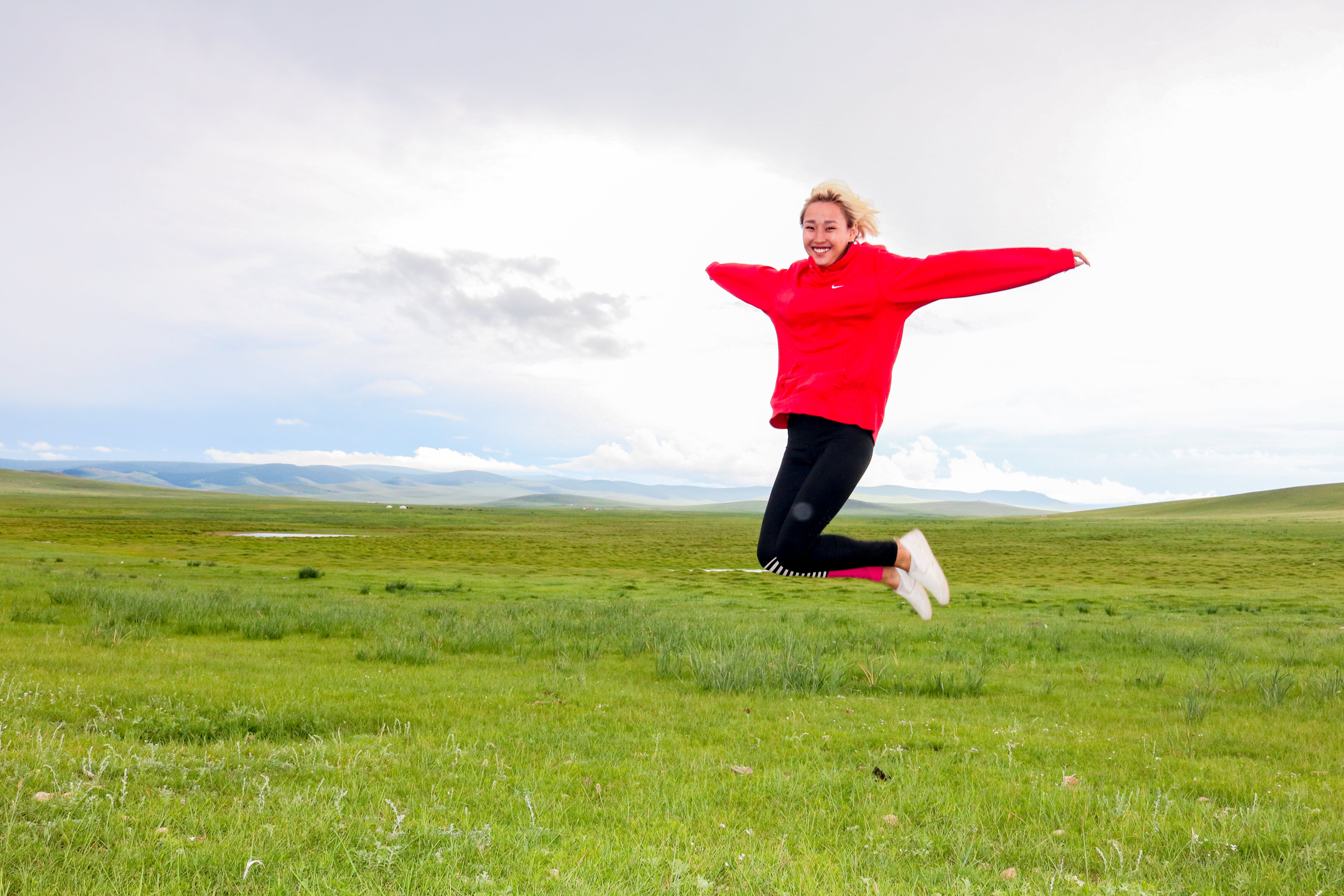 Photo of Woman Jumping on Grass Field