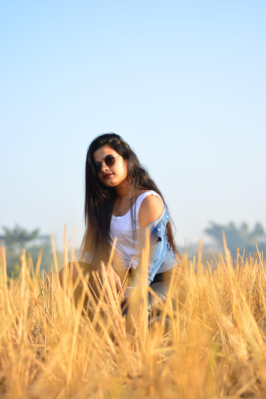 Woman Kneeling on Brown Grass