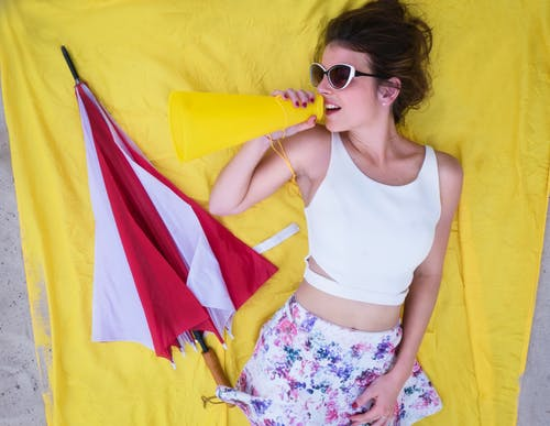 Woman In White Tank Top Laying On Yellow Textile