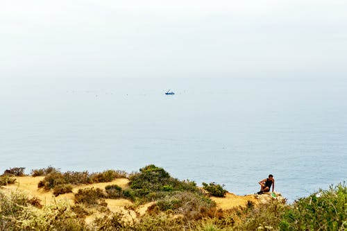 Man Sitting On Cliff