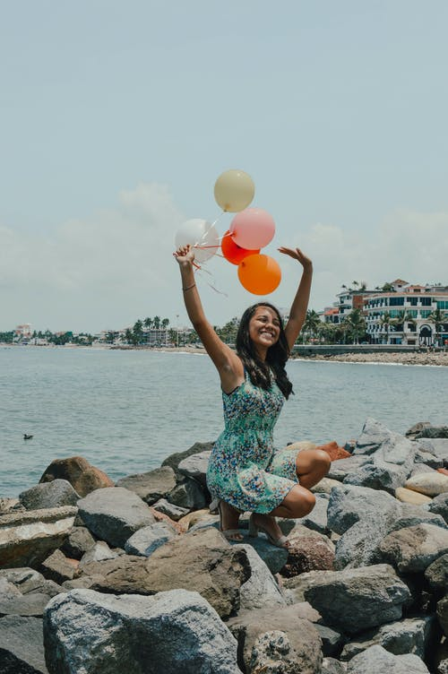 Woman Sitting While Holding Balloons Near Body of Water