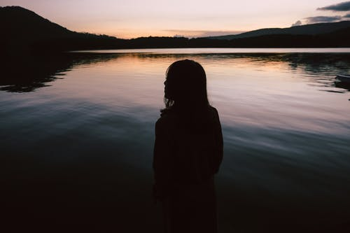 Silhouette Of Woman Standing Near Body Of Water