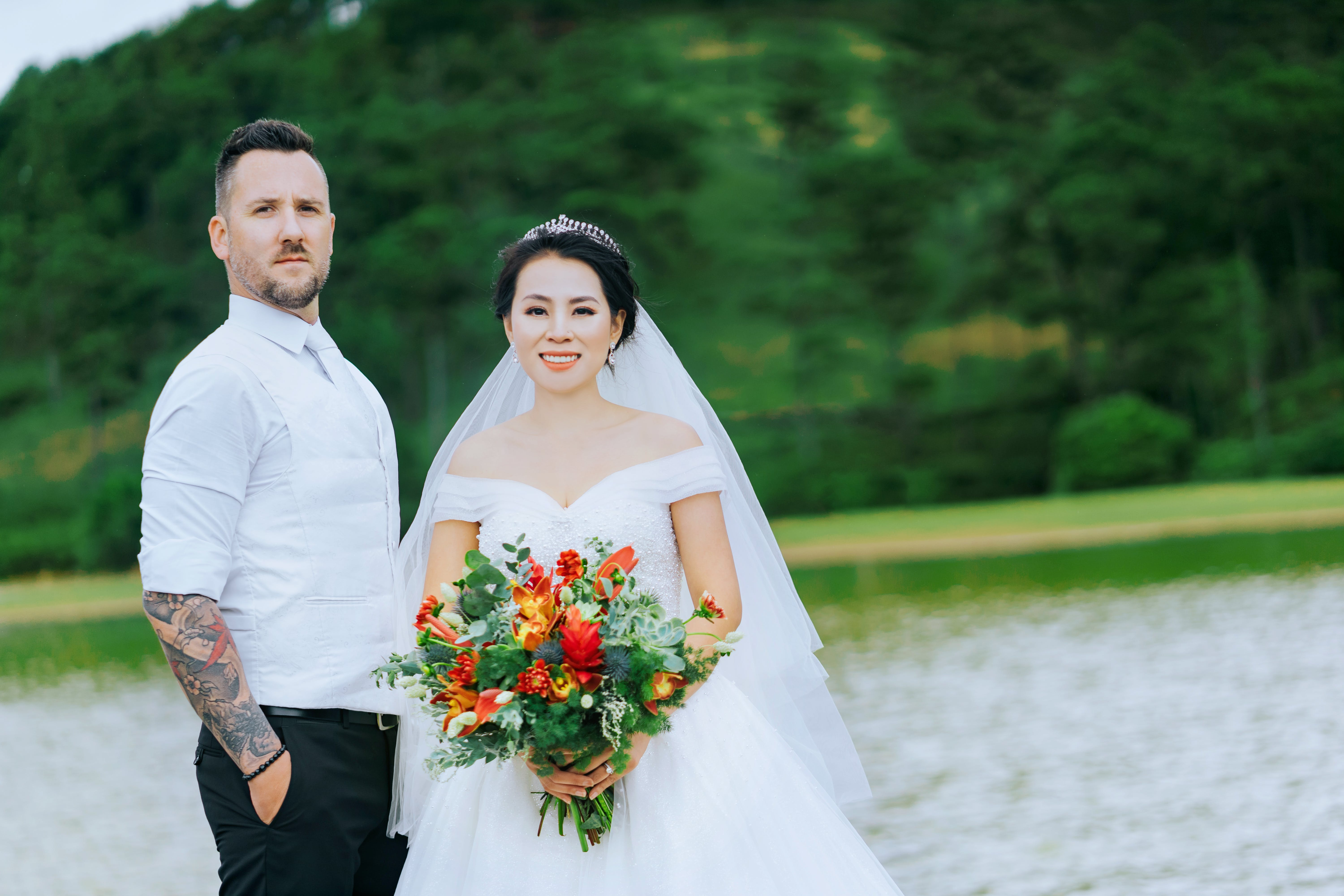 Man Standing Beside Bride Holding Bouquet Of Flowers