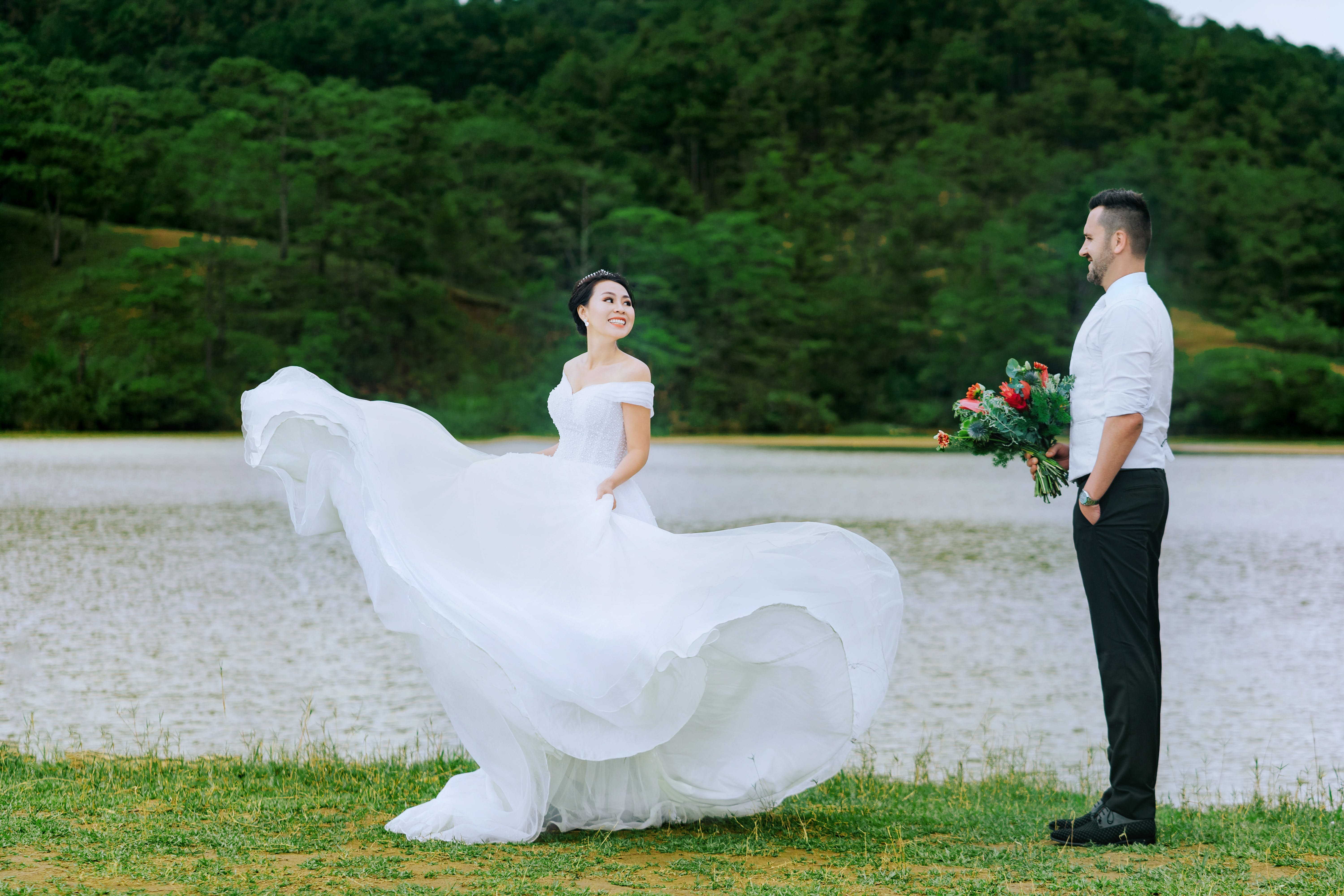 Bride Standing in Front of Groom Holding Bouquet of Flowers