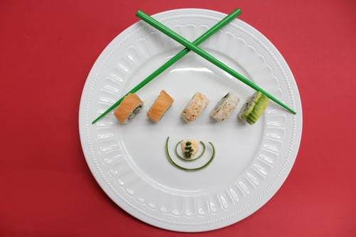 Sushi On White Ceramic Plate With Green Chopsticks