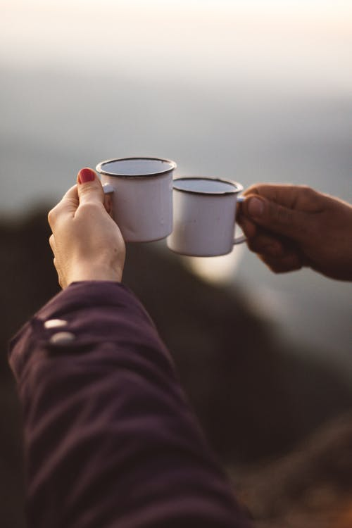 Person Holding Two White Cups