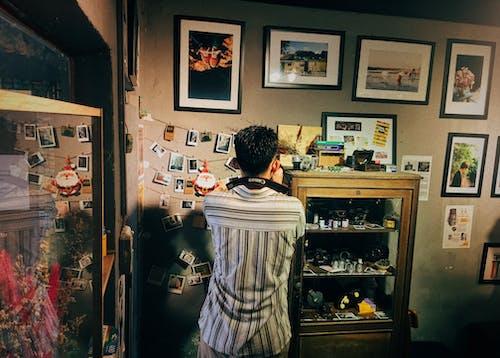 Mann Gegenüber Fotos An Der Wand Befestigt