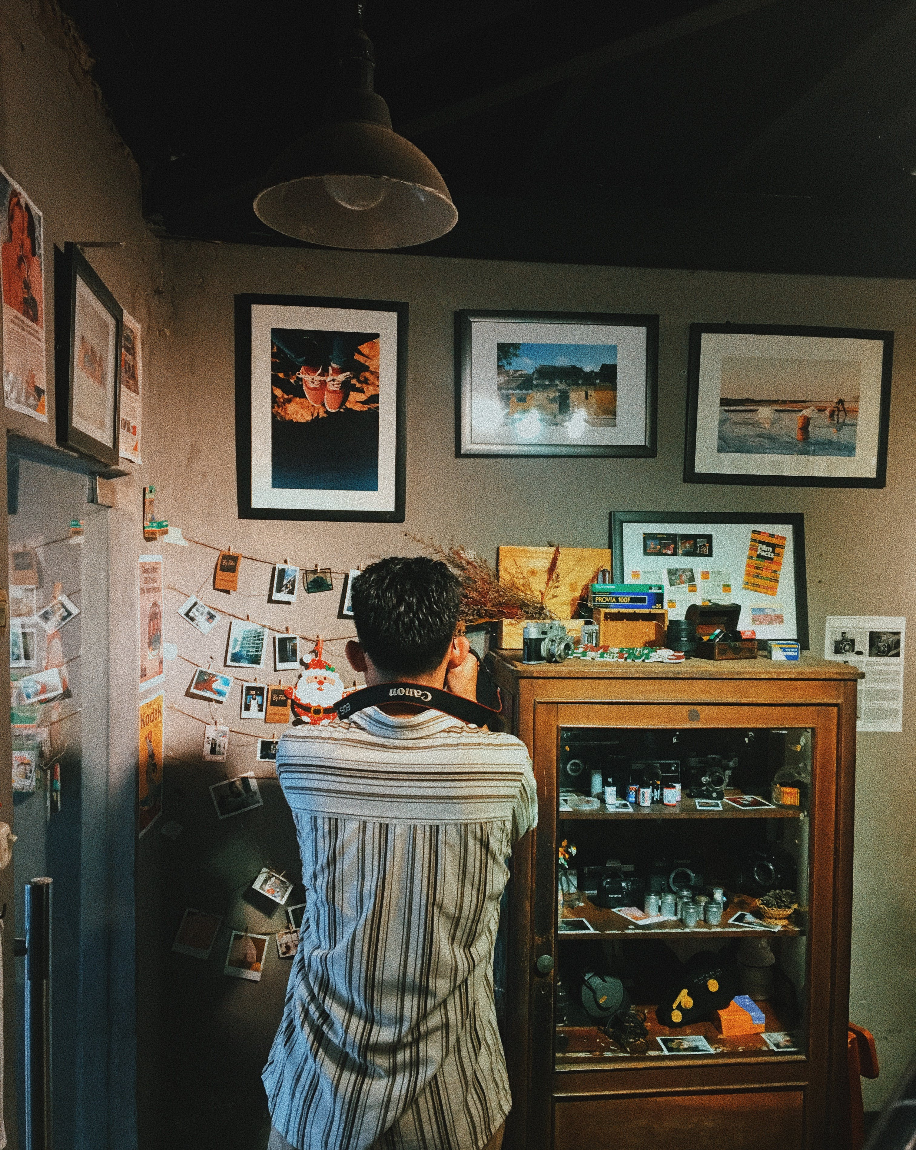 Man Taking Photos of a Wall full of photographs