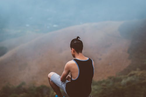 Man Sitting on Top of Hill