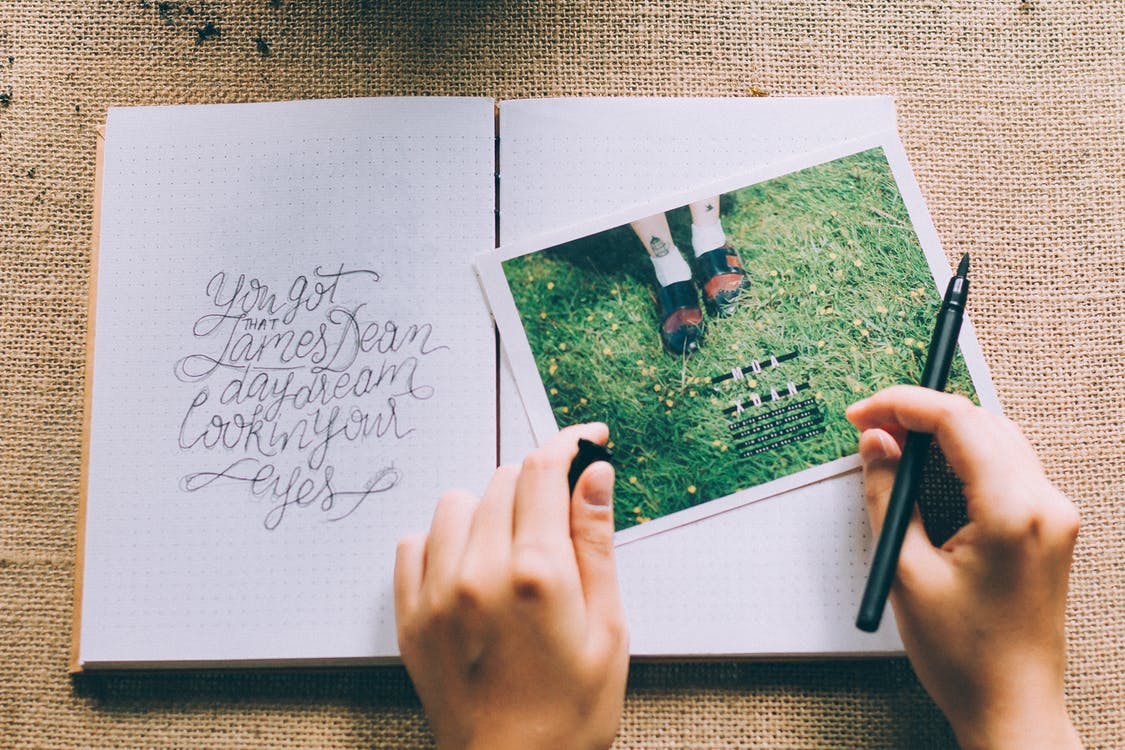 Person Holding Black Marker Beside Photo on Book
