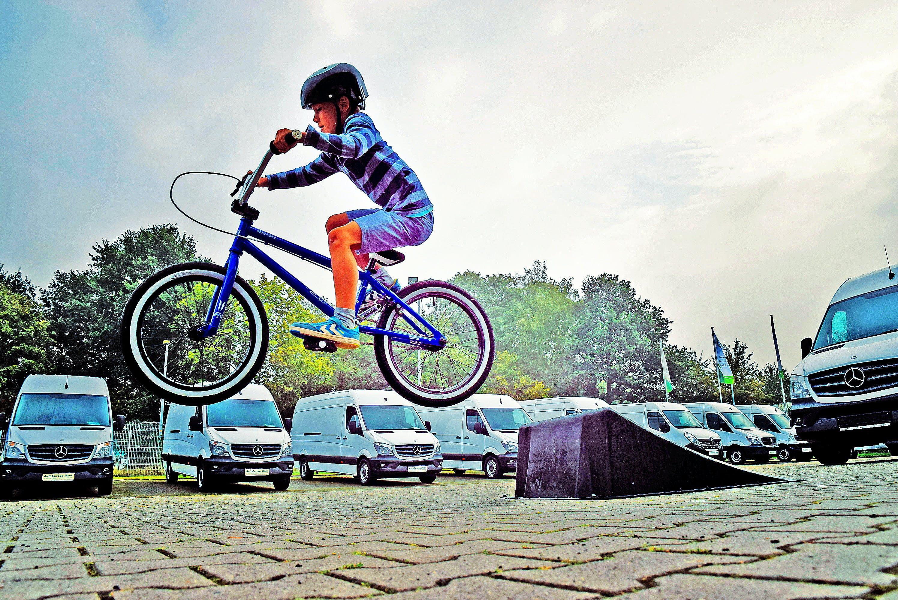 Boy in Black Nutshell Helmet on Blue Bmx Bike Having Hangtime After Taking Off on Ramp