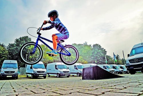 Boy in Black Nutshell Helmet on Blue Bmx Bike Having Hangtime After Taking Off on Ramp