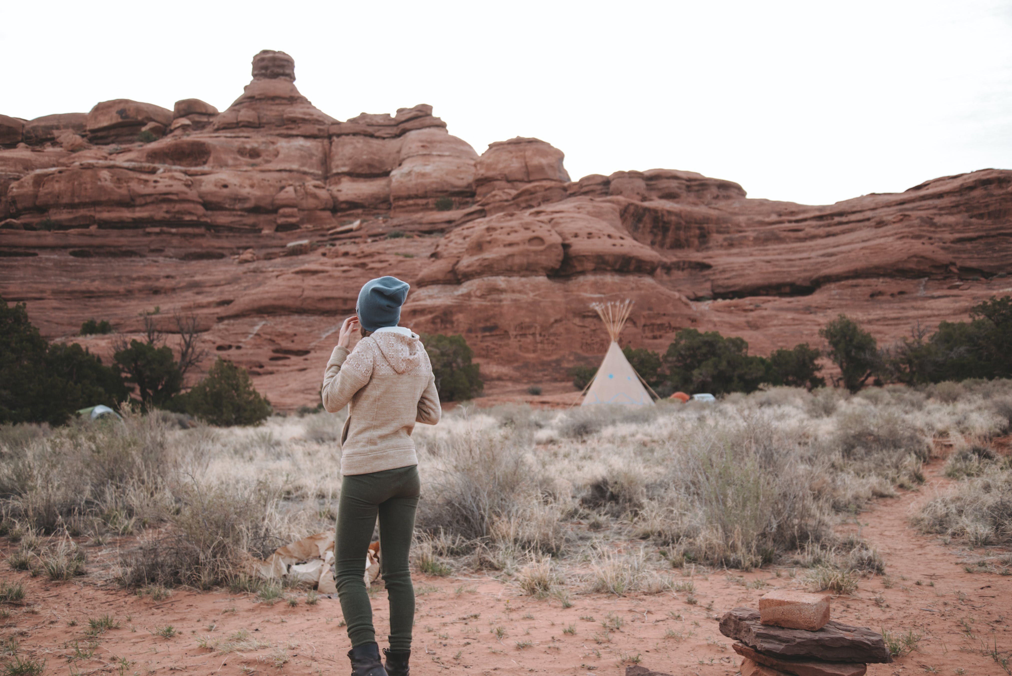 Woman Standing Near Tent and Rock Formation