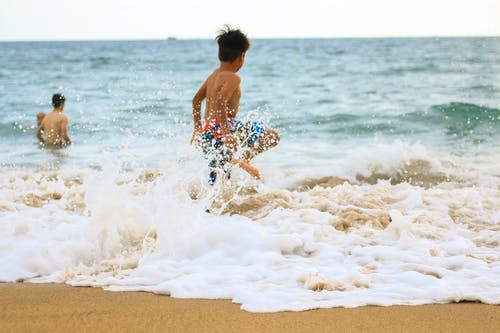 Photo of Boy Rushing Towards Sea