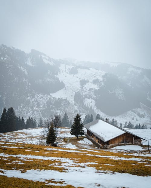 House Near Mountain Covered With Snow